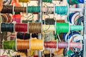 Set of spools with leather rope of different colors for sewing or crafting on  market