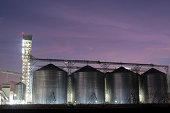 Set of storage tanks raw material agricultural crops feed mills at twilight