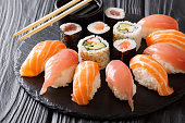 set of sushi and rolls with salmon and tuna, avocado, california, maki, soy sauce, chopsticks close-up on a black stone board on a table. horizontal