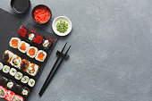 Japanese restaurant, sushi roll on black slate plate. Set for one person with chopsticks, ginger, wasabi, soy sauce, top view, copy space