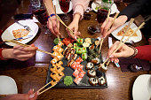 A set of sushi rolls on a table in a restaurant. A party of friends eating sushi rolls using bamboo sticks.