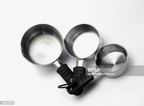 Set of three stainless steel measuring cups, close-up