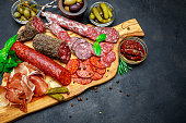Set of traditional Italian meat snack. Salami, prosciutto, olives, capers, pickles on concrete background