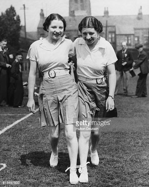 A set of twins practice for a three legged race Miss Betty Howard and Miss Joan Howard both waitresses in the same cafe at Manchester are keen...