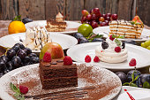 Set of various desserts on a wooden table decorated with fruits and berries.
