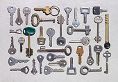 Set of various keys on rough concrete surface close-up, isolated objects, background