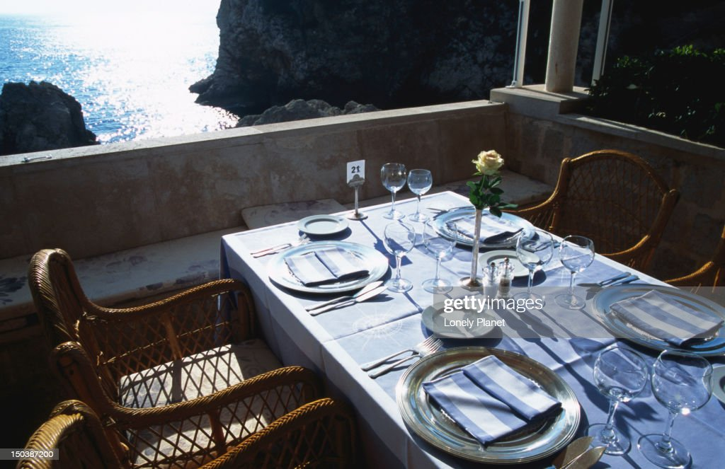 Set tables outside at Restaurant Nautika with sea in background. : Stock Photo