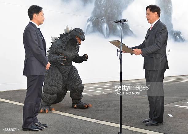 Setagaya Mayor Nobuto Hosaka presents a certificate of commendation to Japan's star monster Godzilla and Toho Co director Minami Ichikawa for...