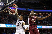 Seth Allen of the Virginia Tech Hokies dunks in front of Malik Beasley of the Florida State Seminoles during the first half in the second round of...