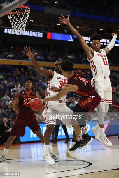 Seth Allen of the Virginia Tech Hokies passes to teammate Zach LeDay against Vitto Brown and Jordan Hill of the Wisconsin Badgers in the second half...