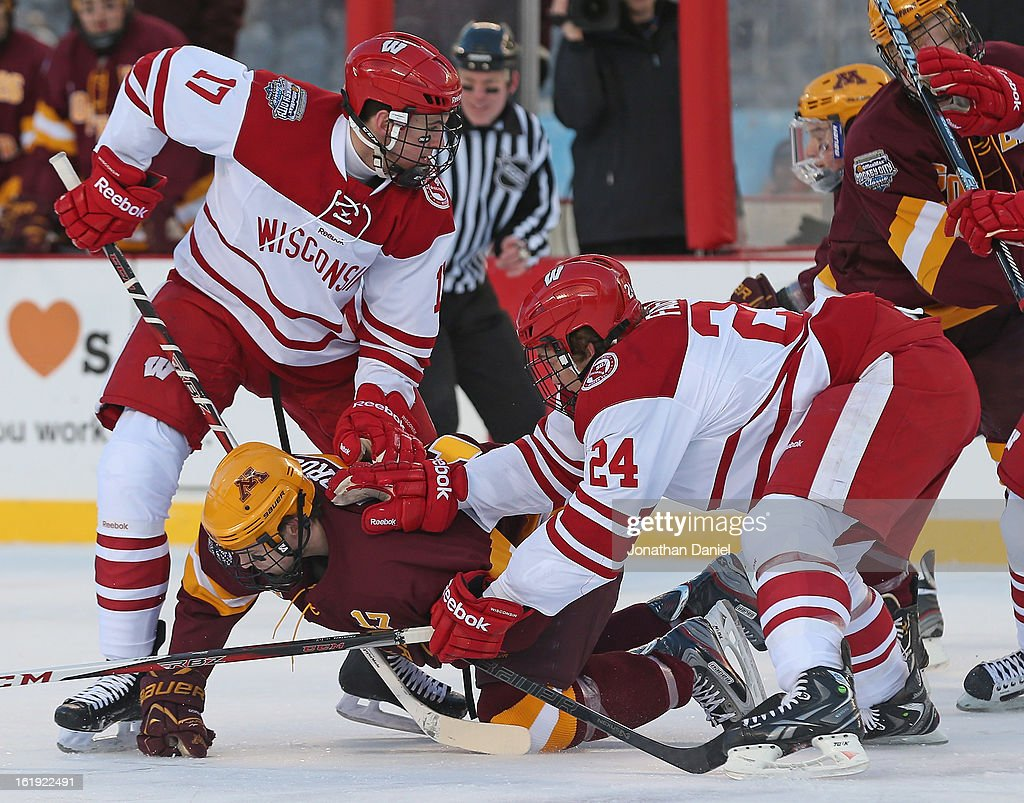 Seth Ambroz #17 of the Minneosta Golden Gophers is shoved to the ice by Joe Faust #24 and Nic Kerdiles #17 of the Wisconsin Badgers during the Hockey City Classic at Soldier Field on February 17, 2013 in Chicago, Illinois.