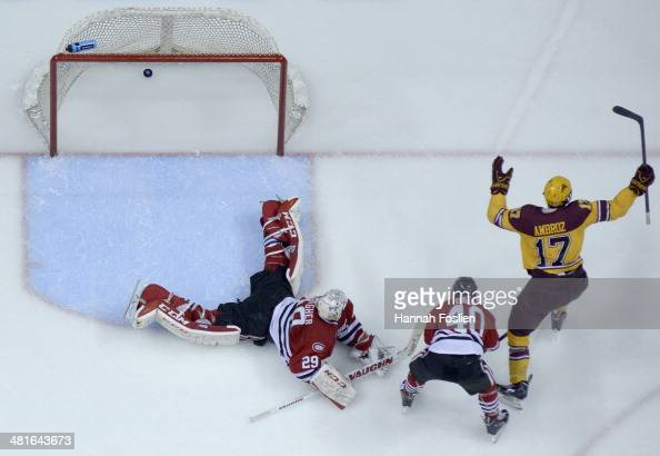 Seth Ambroz of the Minnesota Golden Gophers celebrates scoring a goal against Ryan Faragher of the St Cloud State Huskies as Tim Daly of Tim Daly of...