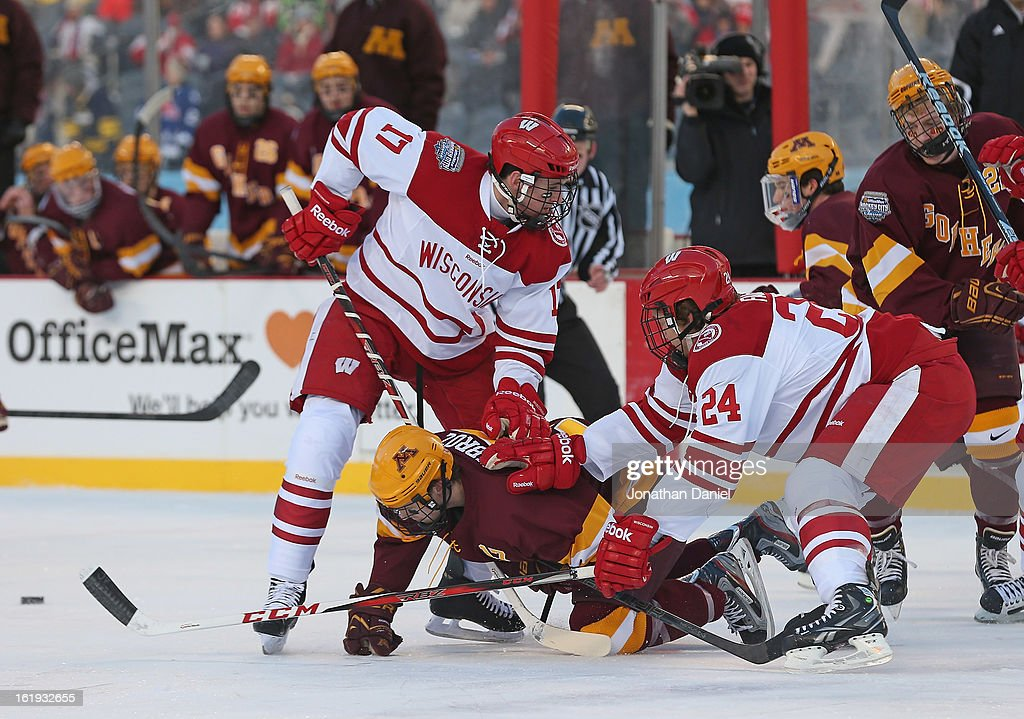 Seth Ambroz #17 of the Minnesota Golden Gophers is shoved to the ice by Joe Faust #24 and Nic Kerdiles #17 of the Wisconsin Badgers during the Hockey City Classic at Soldier Field on February 17, 2013 in Chicago, Illinois.