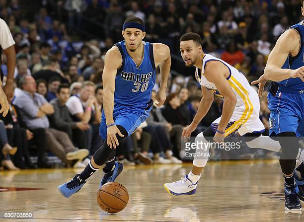 Seth Curry of the Dallas Mavericks dribbles past his brother Stephen Curry of the Golden State Warriors at ORACLE Arena on December 30 2016 in...
