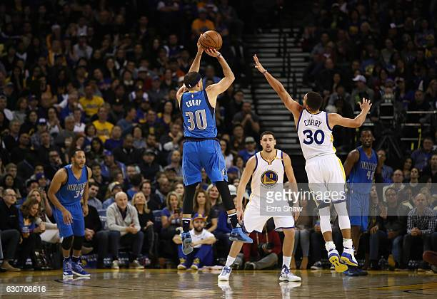 Seth Curry of the Dallas Mavericks shoots over his brother Stephen Curry of the Golden State Warriors at ORACLE Arena on December 30 2016 in Oakland...