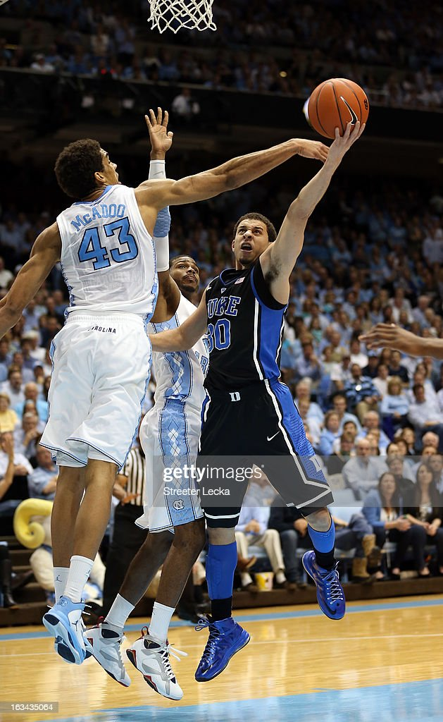 Seth Curry #30 of the Duke Blue Devils drives to the basket against James Michael McAdoo #43 and teammate Dexter Strickland #1 of the North Carolina Tar Heels during their game at the Dean E. Smith Center on March 9, 2013 in Chapel Hill, North Carolina.