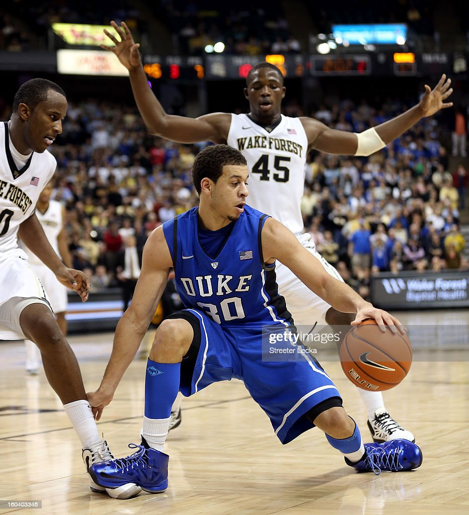 Seth Curry #30 of the Duke Blue Devils keeps the ball away from Arnaud William Adala Moto #45 of the Wake Forest Demon Deacons during their game at Lawrence Joel Coliseum on January 30, 2013 in Winston-Salem, North Carolina.