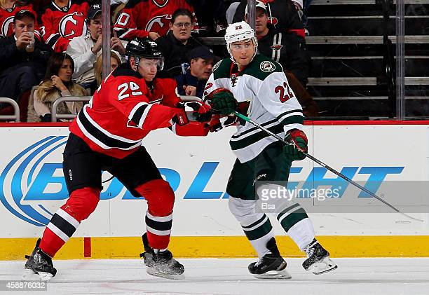 Seth Helgeson of the New Jersey Devils and Nino Niederreiter of the Minnesota Wild fight for position on November 11 2014 at the Prudential Center in...