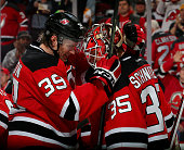 Seth Helgeson of the New Jersey Devils celebrates the win with teammate Cory Schneider after the win over the Edmonton Oilers on February 9 2016 at...