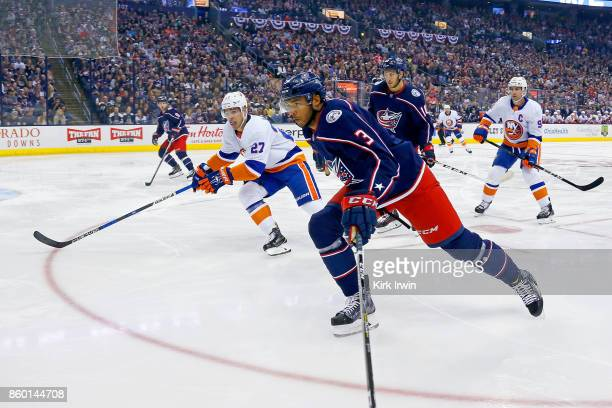 Seth Jones of the Columbus Blue Jackets and Anders Lee of the New York Islanders skate after the puck during the game on October 6 2017 at Nationwide...