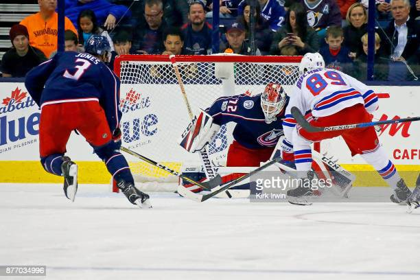 Seth Jones of the Columbus Blue Jackets attempts to knock the puck away away from Pavel Buchnevich of the New York Rangers and Sergei Bobrovsky of...
