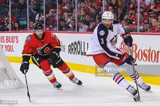 Seth Jones of the Columbus Blue Jackets carries the puck against TJ Brodie of the Calgary Flames during an NHL game at Scotiabank Saddledome on...