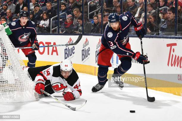 Seth Jones of the Columbus Blue Jackets skates after a loose puck as Miles Wood of the New Jersey Devils falls to the ice during the second period of...