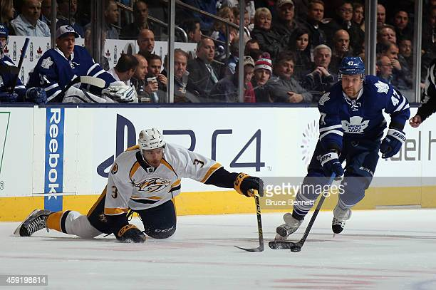 Seth Jones of the Nashville Predators dives for the puck as Leo Komarov of the Toronto Maple Leafs moves down ice during the first period at the Air...
