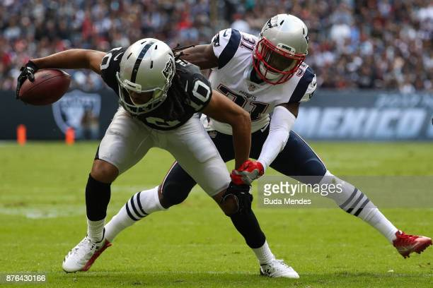 Seth Roberts of the Oakland Raiders attempts to break a tackle from Jonathan Jones of the New England Patriots during the first half at Estadio...
