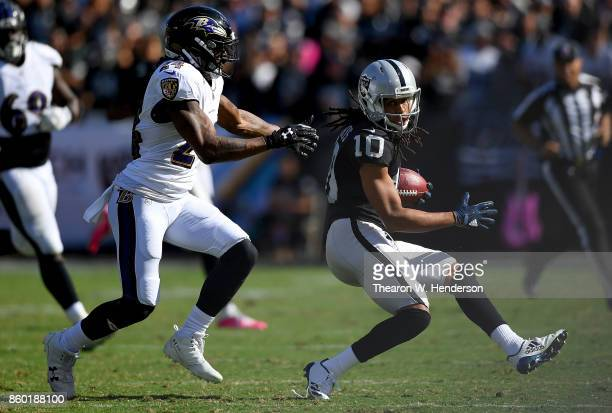 Seth Roberts of the Oakland Raiders looks to avoid the tackle of Brandon Carr of the Baltimore Ravens during the third quarter of their NFL football...