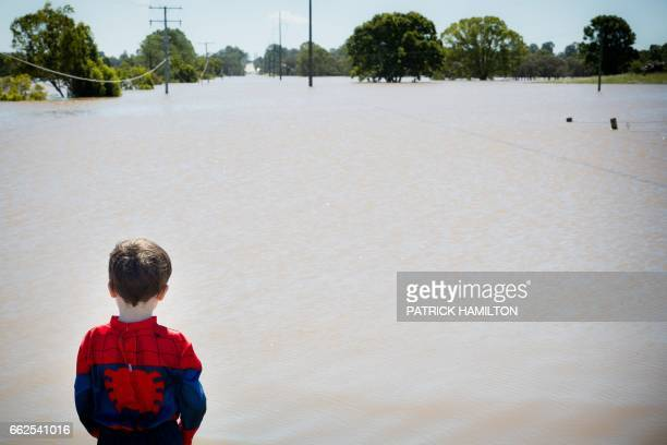 TOPSHOT Seth Skirving watches floodwaters of the Logan River caused by Cyclone Debbie flow over the Mt Lindesay Highway in Waterford West near...