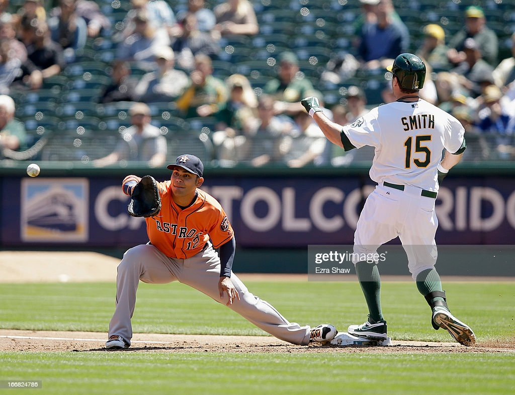 <a gi-track='captionPersonalityLinkClicked' href=/galleries/search?phrase=Seth+Smith&family=editorial&specificpeople=3190174 ng-click='$event.stopPropagation()'>Seth Smith</a> #15 of the Oakland Athletics beats the ball to first base for an infield hit in the first inning of their game against the Houston Astros at O.co Coliseum on April 17, 2013 in Oakland, California. Carlos Pena #12 of the Houston Astros waits for the ball at first base.