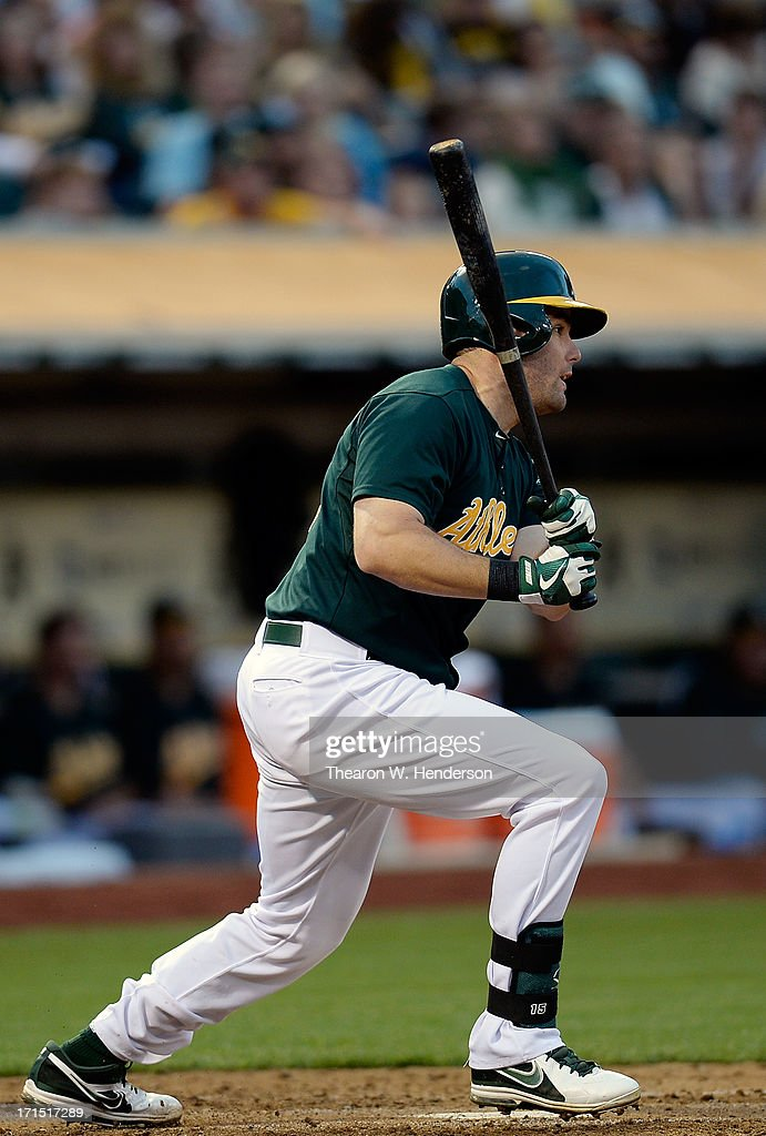 Seth Smith #15 of the Oakland Athletics hits an RBI single scoring Coco Crisp #4 in the fourth inning against the Cincinnati Reds at O.co Coliseum on June 25, 2013 in Oakland, California.