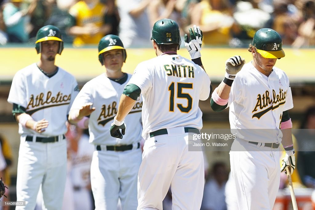 <a gi-track='captionPersonalityLinkClicked' href=/galleries/search?phrase=Seth+Smith&family=editorial&specificpeople=3190174 ng-click='$event.stopPropagation()'>Seth Smith</a> #15 of the Oakland Athletics is congratulated by teammates after hitting a home run against the Detroit Tigers during the fifth inning at O.co Coliseum on May 13, 2012 in Oakland, California. The Detroit Tigers defeated the Oakland Athletics 3-1.