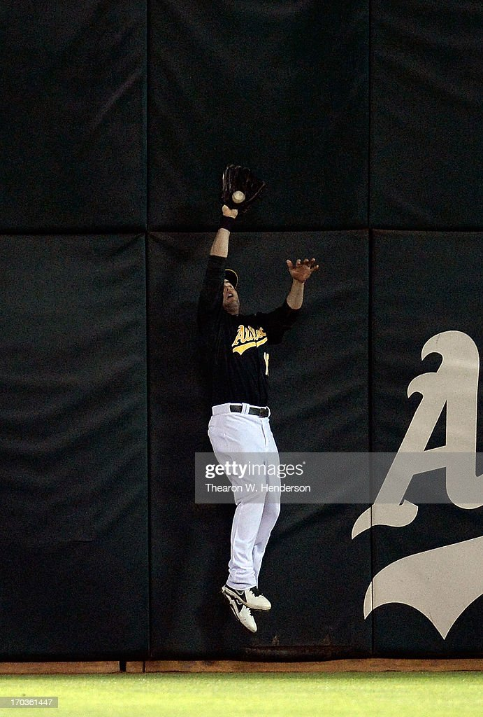 <a gi-track='captionPersonalityLinkClicked' href=/galleries/search?phrase=Seth+Smith&family=editorial&specificpeople=3190174 ng-click='$event.stopPropagation()'>Seth Smith</a> #15 of the Oakland Athletics leaps up against the left centerfield wall to take a hit away from Travis Hafner #33 of the New York Yankees for the final out of the game in the ninth inning at O.co Coliseum on June 11, 2013 in Oakland, California. The Athletics won the game 6-4.