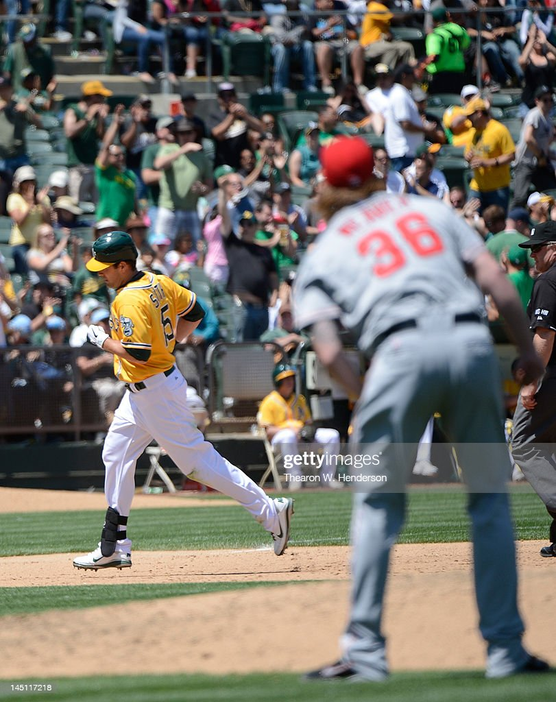 <a gi-track='captionPersonalityLinkClicked' href=/galleries/search?phrase=Seth+Smith&family=editorial&specificpeople=3190174 ng-click='$event.stopPropagation()'>Seth Smith</a> #15 of the Oakland Athletics trots around the bases after hitting a solo home run while pitcher <a gi-track='captionPersonalityLinkClicked' href=/galleries/search?phrase=Jered+Weaver&family=editorial&specificpeople=565100 ng-click='$event.stopPropagation()'>Jered Weaver</a> #36 of the Los Angeles Angels of Anaheim looks on in the six inning at O.co Coliseum on May 23, 2012 in Oakland, California.
