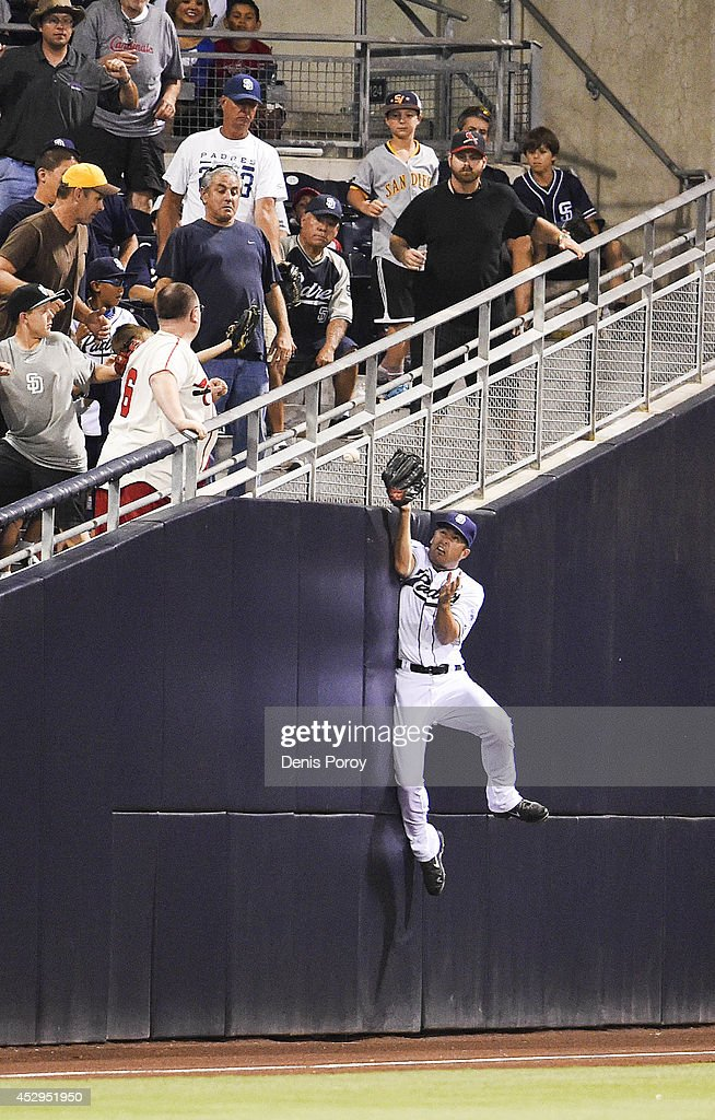 Seth Smith #12 of the San Diego Padres jumps but can't make the catch on a foul ball hit by Matt Carpenter #13 of the St. Louis Cardinals during the sixth inning of a baseball game at Petco Park July 30, 2014 in San Diego, California.