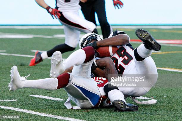 Seth Williams of the Ottawa Redblacks tackles Chad Johnson of the Montreal Alouettes during the CFL game at Percival Molson Stadium on June 20 2014...