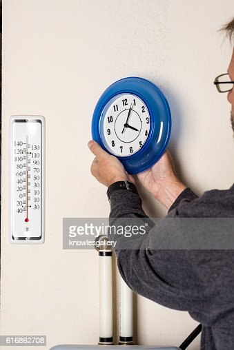 Setting a clock by one hour for daylight savings : Stock Photo
