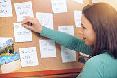 Shot of a young woman pinning notes on a corkboard at home