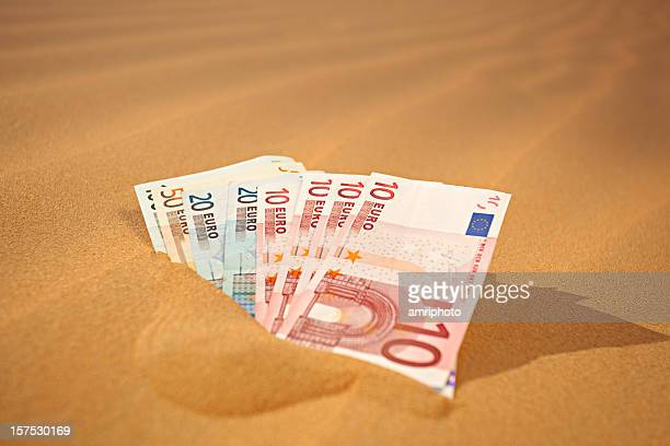 setting money into sand - german phrase