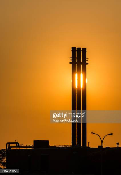 Setting sun behind 3 chimneys