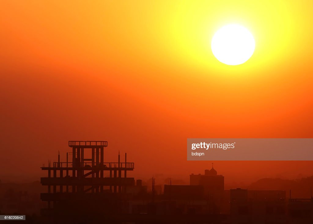 Setting sun behind construction building : Stock-Foto
