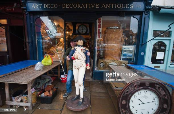 Setting up for Saturday trade at one of the antique shops it Portobello Road on January 16 2010 in London England Portobello traders fear for the...