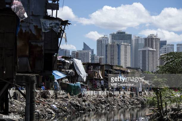 A settlement is seen in the foreground as the skyline of Manila's financial district is seen behind it on August 17 2017 The Philippine economy grew...