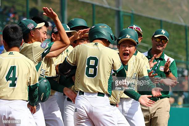 Seum Kwon of the AsiaPacific Team from South Korea is greeted by his teammates after hitting a home run against the Mexico Team at Lamade Stadium...