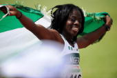Seun Adigun of Nigeria celebrates with the Nigerian flag after crossing the finish line in first place in the Women's 100 meters Hurdles final during...