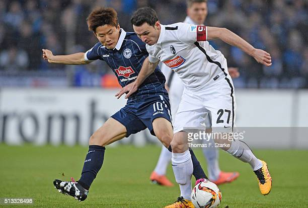 Seung Woo Ryu of Bielefeld and Nicolas Hoefler of Freiburg fight for the ball during the Second Bundesliga match between Arminia Bielefeld and SC...