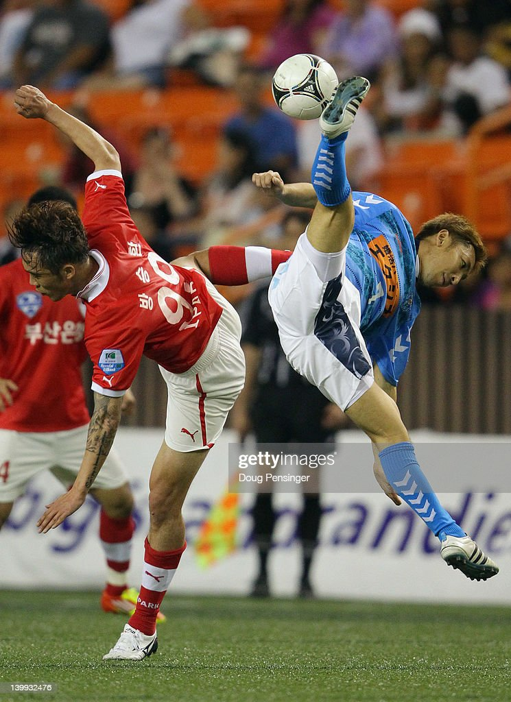 Seungwhan Bang #99 of Busan I'Park FC (Korea) and Tomoya Uchida #7 of Yokohama FC (Japan) collide as they vie for the ball in the Championship Match of the Hawaiian Islands Invitational Soccer Tournament at the Aloha Stadium on February 25, 2012 in Honolulu, Hawaii.