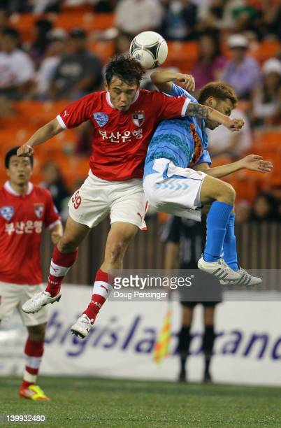 Seungwhan Bang of Busan I'Park FC and Tomoya Uchida of Yokohama FC collide as they vie for the ball in the Championship Match of the Hawaiian Islands...